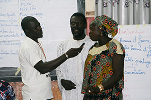 A reporter from Alfayda FM radio records Momath Diop and his wife give a testimonial about how he helps his wife fetch water, clean, and care for their children during a January 2017 gender training in Kaolack Region.