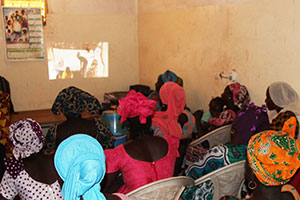 Community members gather at their local health facility to watch a video on best practices for complementary feeding.