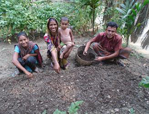 Photo of Nasima and three members of her family in a vegetable garden.
