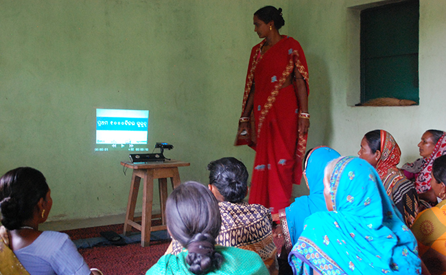 Photo of a group of women watching a video on a wall inside