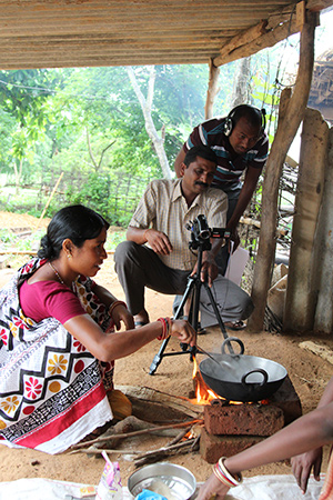 Photo of two men filming a woman cooking in a pot