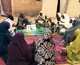 Women sit on rugs and discuss behavior change.