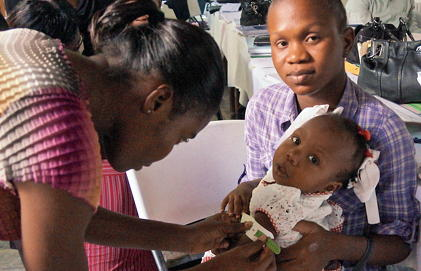 A health workers bends down to touch a baby in her mother's arms.
