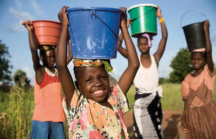 Children carry buckets of water on their heads.