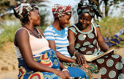 Three women smile together in Sierra Leone.