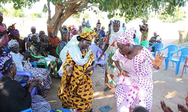 Women dance under a tree to as part of the lively celebration.