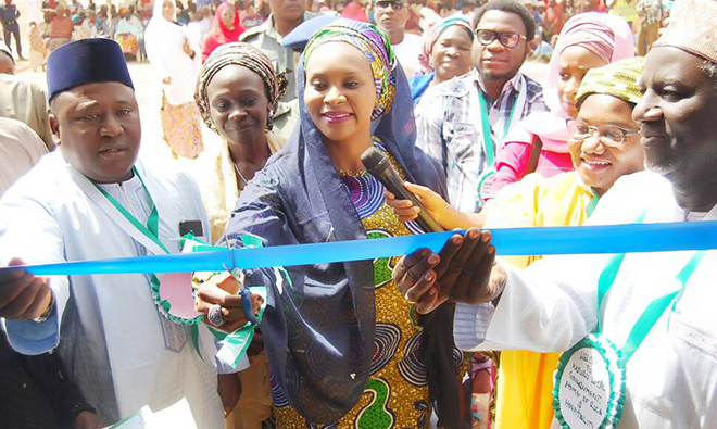 Photo of men and women reaching out and cutting a blue ceremonial ribbon.