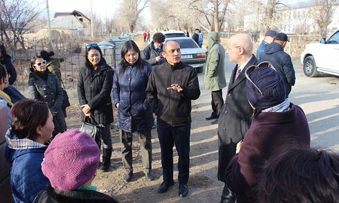 Chargé d'Affaires Alan Meltzer discusses SPRING's community approach with project staff and volunteers before the household visit.