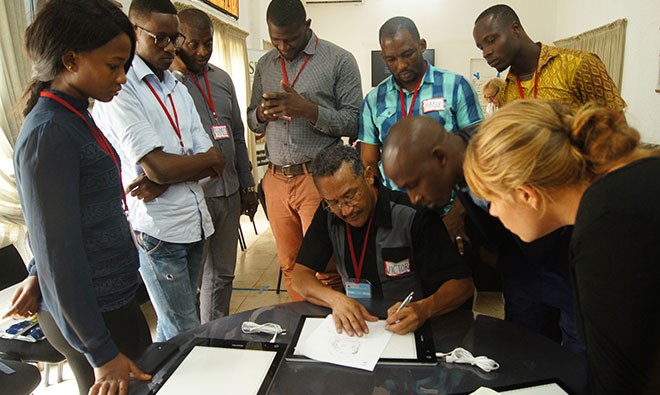 A group of artists gathers around the trainer who is demonstrating how to trace an image.