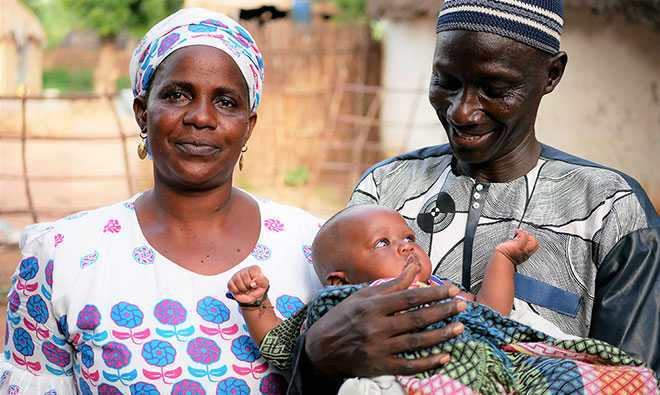 A man and woman stand in front of the camera. The woman looks ahead, the man looks and smiles at their baby in his arms
