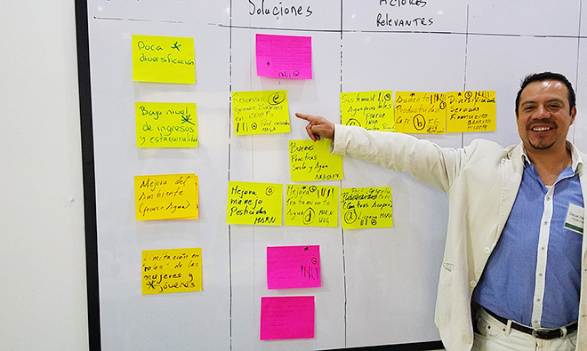 Photo of a man pointing to a board with many brightly colored written cards posted.
