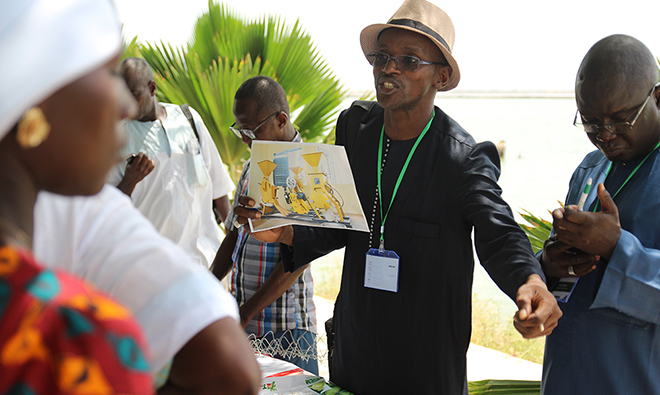 Photo: SPRING/Senegal's Agriculture/Markets Officer, Mamadou Ba, holds up a photo of one of the cereal processing units that SPRING helped install in communities.