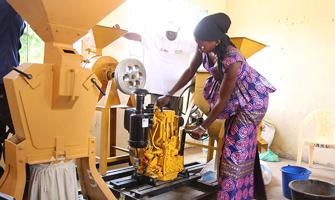 A trainee practices starting the motor of a cereal processor.