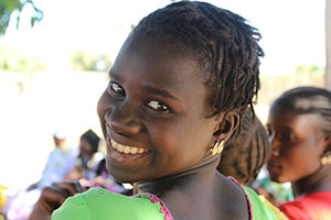 an adolescent girl looks backward over her shoulder and smiles broadly