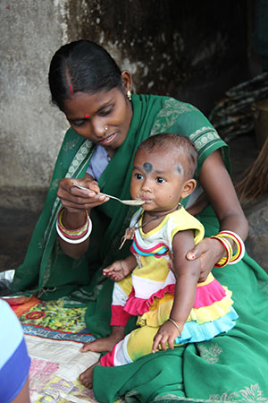 An Indian woman feeds her young child