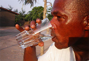 Photo of a man drinking water outside.