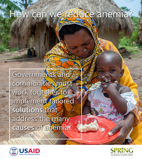 A woman sits on the ground with a hut in the background. She leans over and focuses intently on her baby whom she is attempting to feed. The baby is more interested in the camera than in the food. The overlay text says: How can we reduce anemia? Governments and communities must work together to implement tailored solutions that address the many causes of anemia.