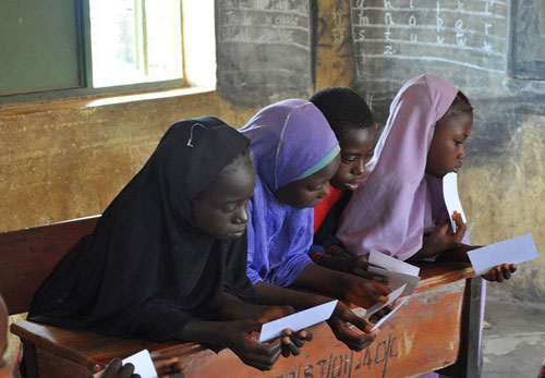 Three Nigerian school girls look at information.