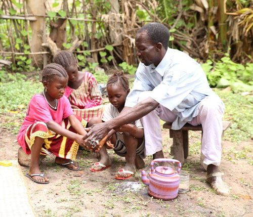 A father helps his children learn to wash their hands.