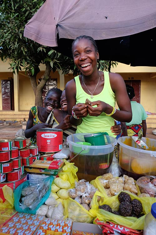 A female entrepreneur in Sierra Leone smiles at the camera.