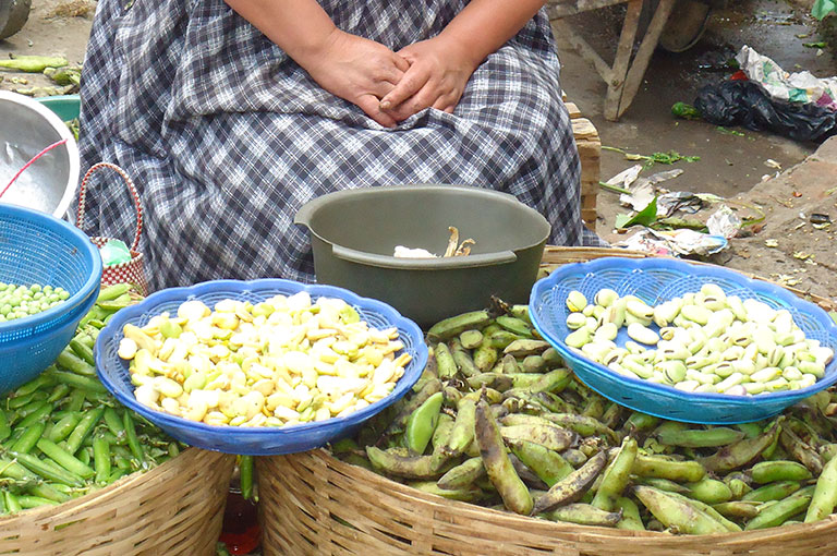 Photo of a woman selling produce at a market.