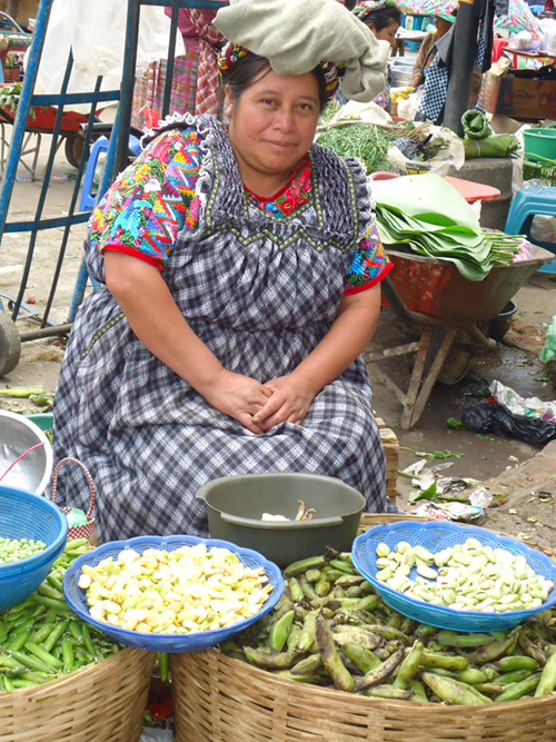 Photo of a woman sitting at her produce stall in an outdoor market.