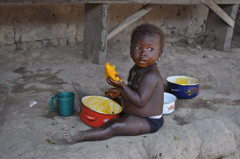 Photo of a child eating on the ground.