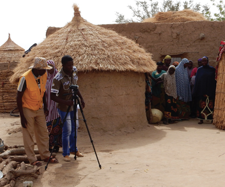 Photo of video crew and villagers outside a hut.