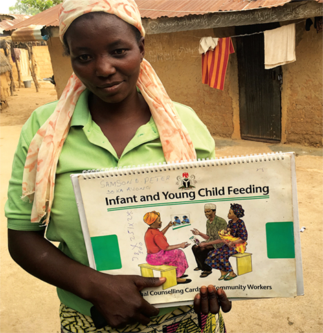 Photo of a woman holding cards related to Infant and Young Child Feeding