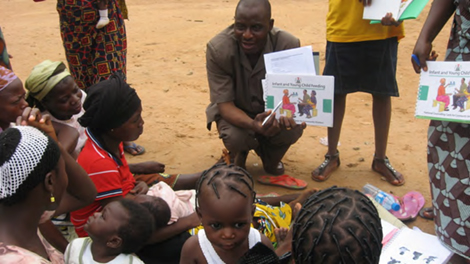 Photo of a man showing several people illustrated materials.