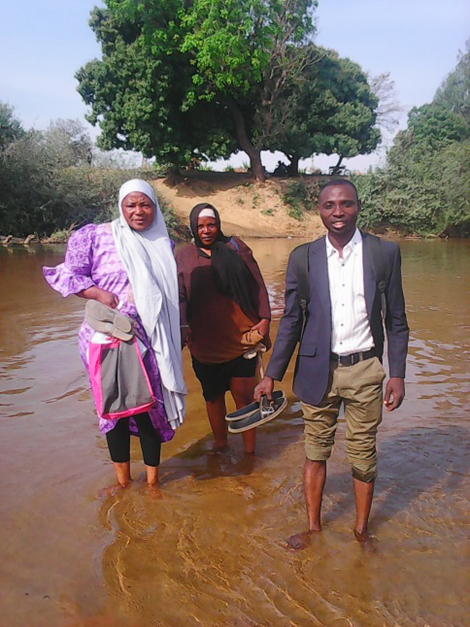 Photo of three people walking into a creek.