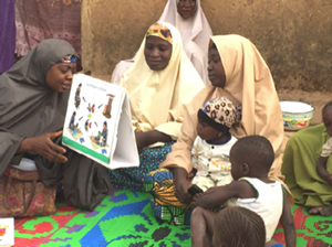 Photo of four women and two infants seated on a rug outside looking at a diagram.