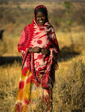 Photo of a woman smiling while standing in a field