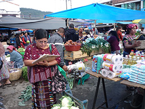 woman with a clipboard walking through a market