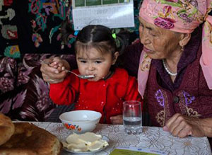 A grandmother helps her young granddaughter eat her food with a spoon.