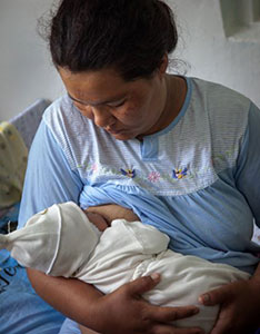 A woman holds and breastfeeds her infant.