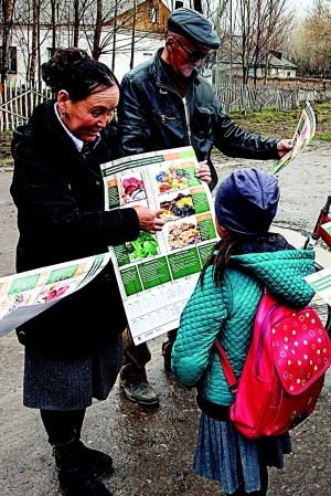 Photo of a woman showing a poster on nutrition to a young girl and her grandparent