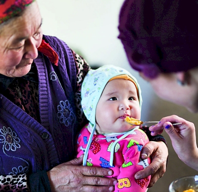 Photo of an infant, held by her grandmother, being fed with a spoon by her mother