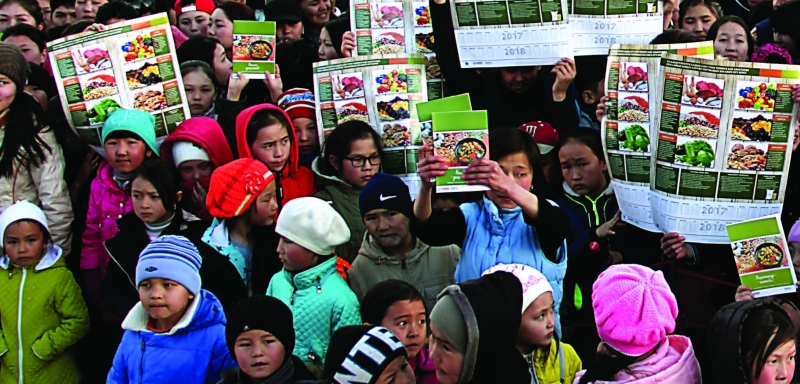 Photo of about thirty or so women and girls, some of whom are holding up posters on nutrition