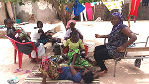A group of women and children sit in chairs and on the ground outside. They are participating in a household interview.