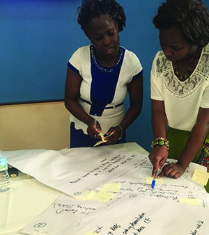 Photo of two women standing at a table writing on large sheets of paper.