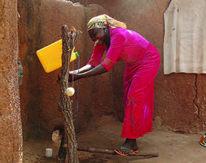 Photo of a woman smiling as she uses a tippy tap.