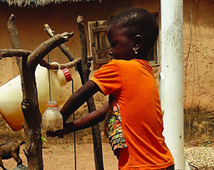 Photo of a young boy using a tippy tap.