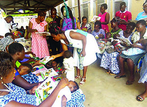 Photo of mothers and children reading through support and health materials.