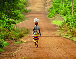 Photo of a woman walking down a long dirt road carrying a package on her head and her child on her back.