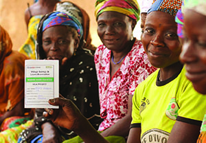"Photo of a group of women sitting, one of whom is holding up a form with USAID|Ghana and SPRING logos titled ""Village Savings and Loans Association."""