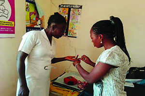 Photo of two female healthcare workers demonstrating anemia testing.