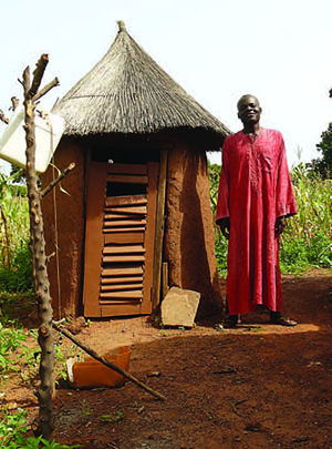 Photo of a man: Abukari Imoro stands by his latrine, which has helped reduce the incidence of disease in his community.