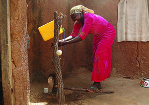 Photo of a woman, caption: Rukaya Mohammed demonstrates handwashing with soap, a vital practice for better health and nutrition.