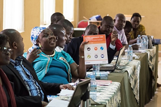 "Photo of about a dozen men and women seated at a table. Caption: ""Participants attend a DATA workshop in Amuria district"""